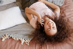 portrait-young-dark-skinned-lady-lying-bed-she-s-room-talking-phone-broadly-smiling-enjoy-sunny-morning-home_295783-8609
